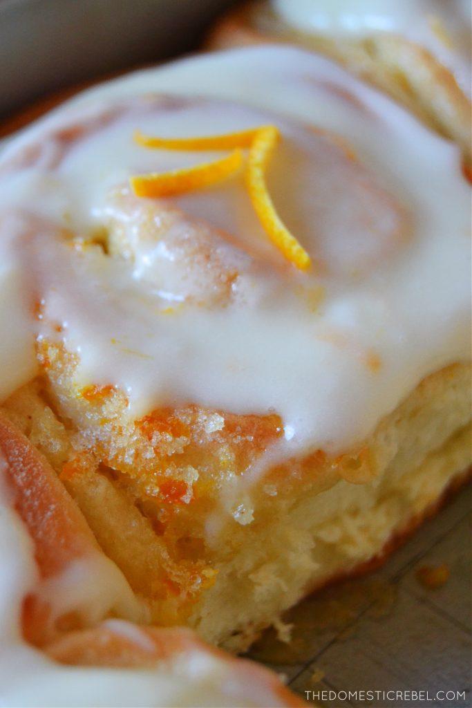 Closeup of an orange sweet roll in a pan with orange zest strips
