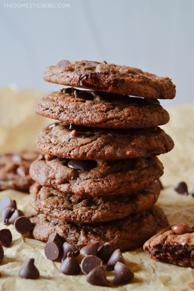 tall stack of chocolate chocolate chip cookies on parchment with choco chips