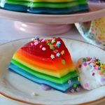 Piece of rainbow jello mold on a white plate