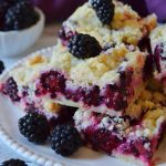 blackberry crumble bars arranged on a white plate