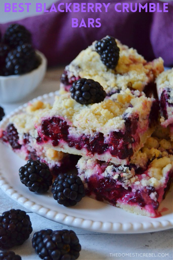 a white plate with a stack of blackberry crumble bars and fresh blackberries