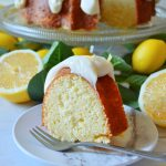 lemon bundt cake on white plate with lemons