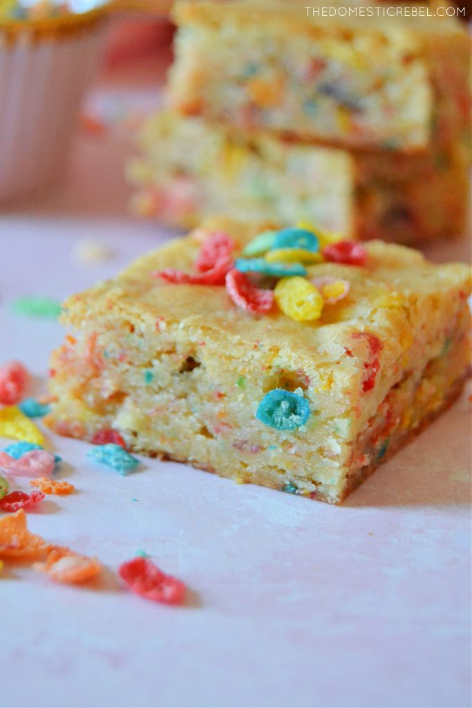 A piece of a fruity pebble blondie on a pink board