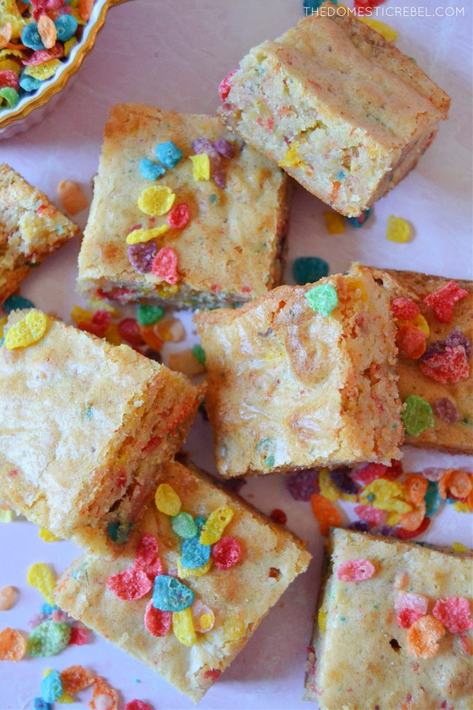 An arrangement of fruity pebble blondies with pieces of cereal