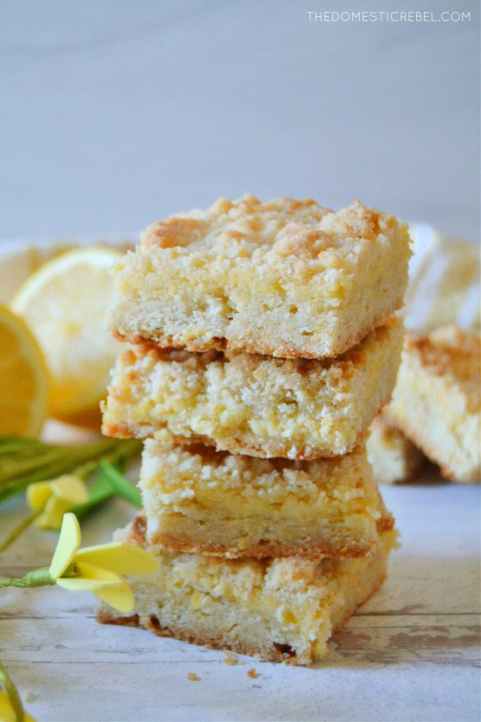 a quadruple stack of lemon crumble bars on white wood