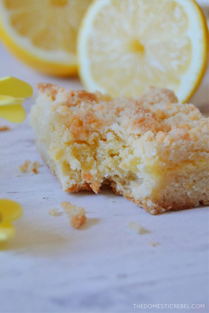 lemon crumble bar with bite missing on white wood