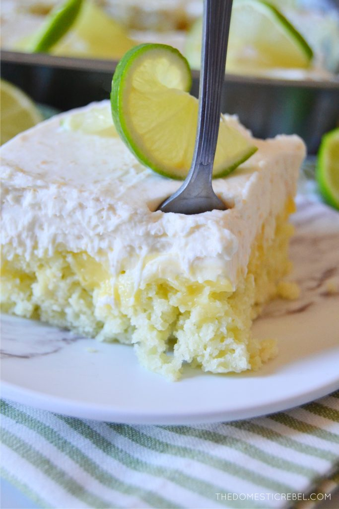 a piece of key lime pie poke cake with a fork in it
