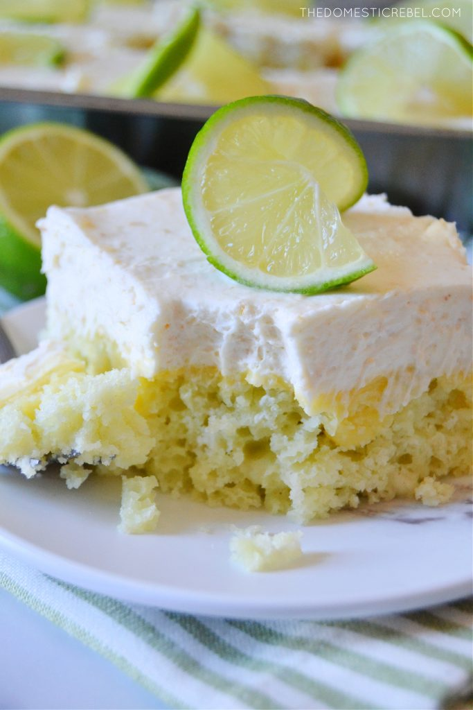 a slice of key lime pie poke cake with a bite missing