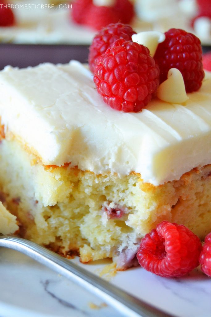 closeup of a piece of white choc raspberry cake with a bite missing