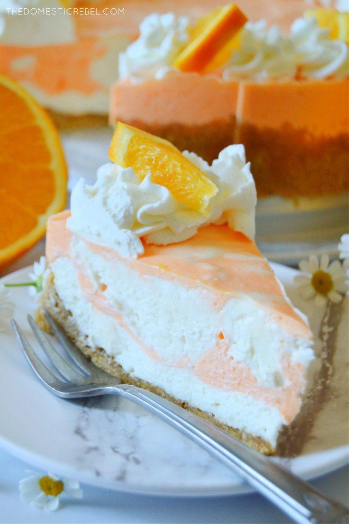 a closeup slice photo of a piece of orange creamsicle cheesecake
