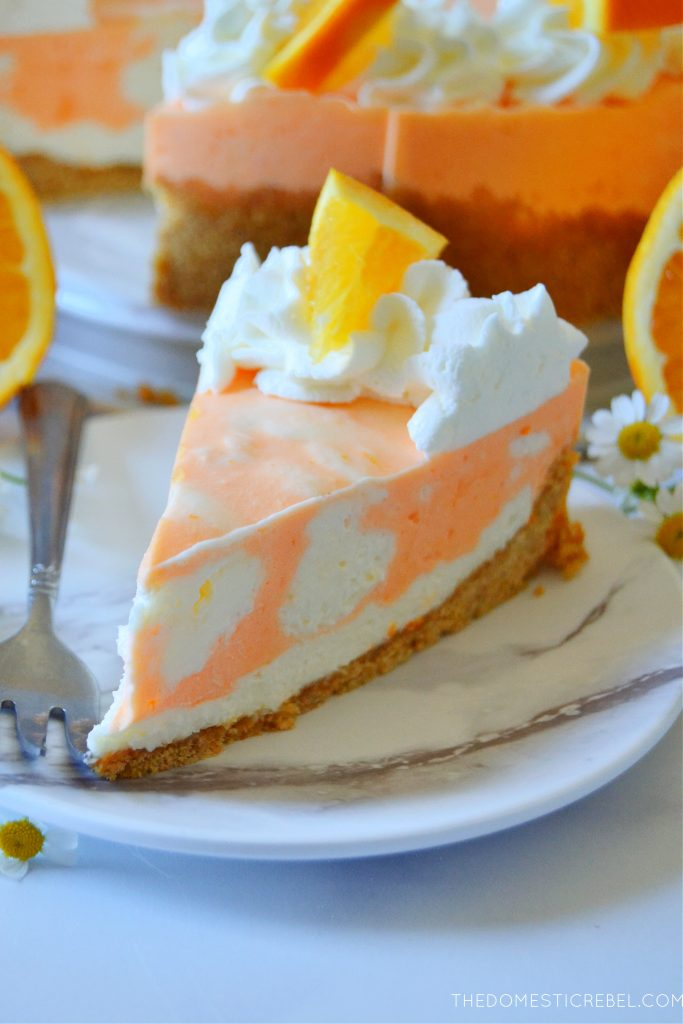 closeup of a slice of orange creamsicle cheesecake on a white marble plate