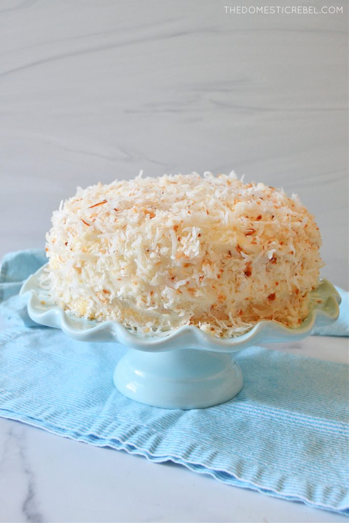 coconut layer cake on a blue cake stand