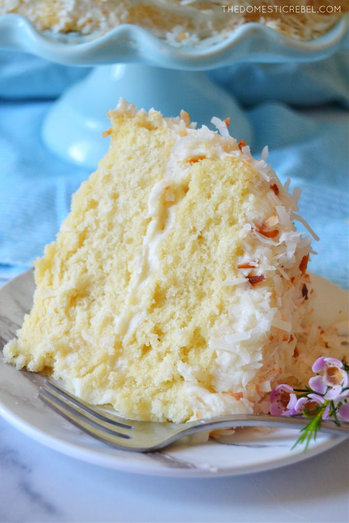 coconut layer cake slice with flowers and a fork on a plate