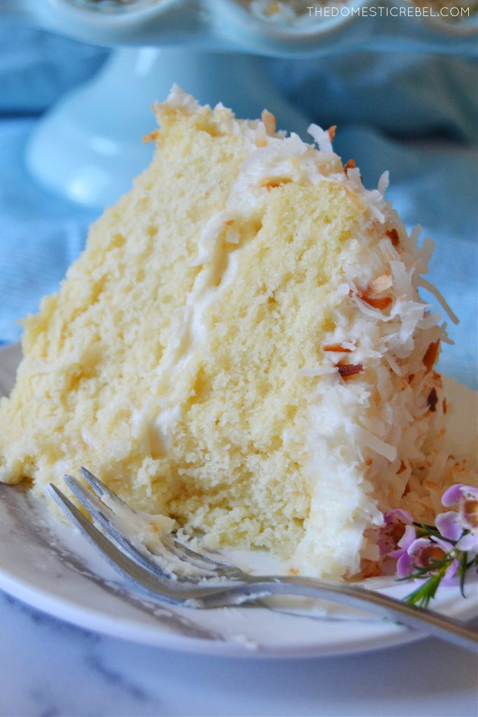 closeup of a slice of coconut layer cake with bite missing