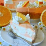 slice of orange creamsicle cheesecake with oranges