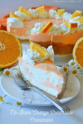 slice of orange creamsicle cheesecake with oranges