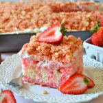 fresh strawberries and a strawberry crunch poke cake piece on a white plate