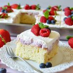 square piece of berries and cream poke cake on a white plate