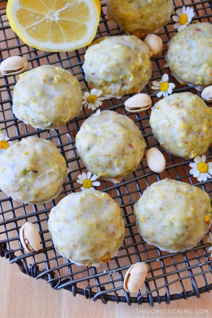 pistachio lemon cookies arranged on a wire rack with pistachios and daisies