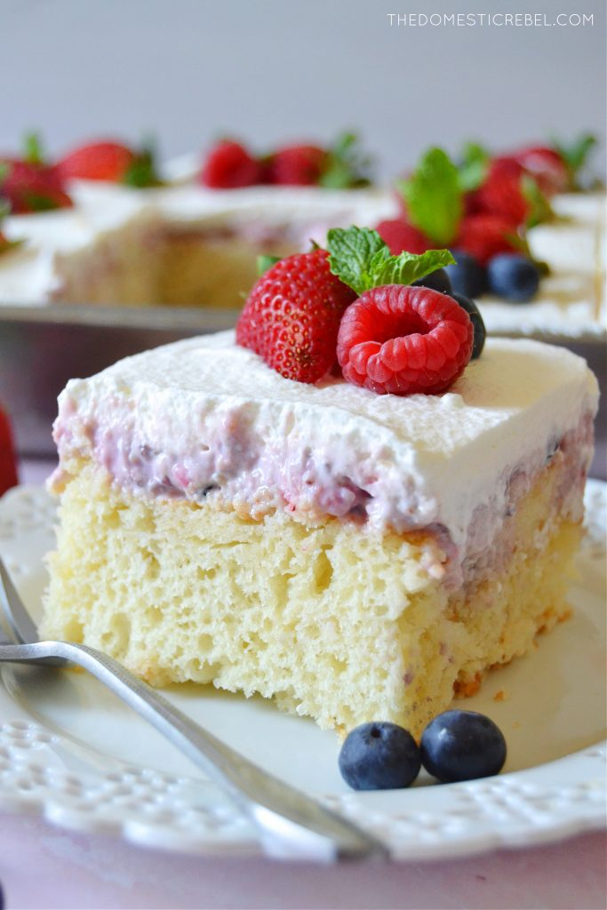 closeup square of berries and cream poke cake on a white plate
