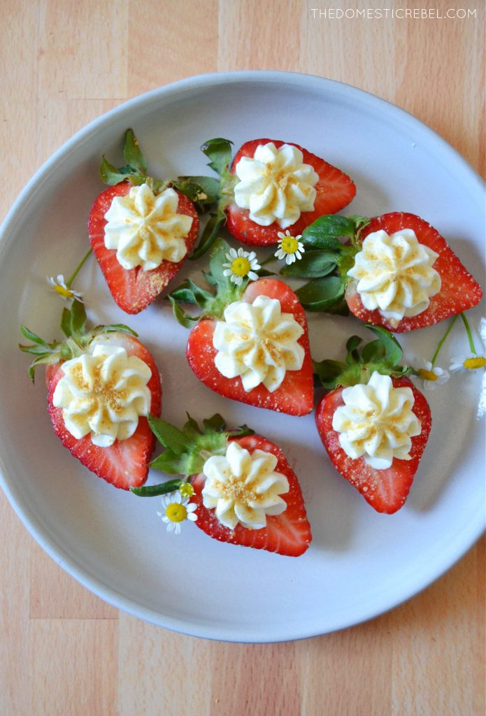 white plate with cheesecake deviled strawberries and little daisies on it