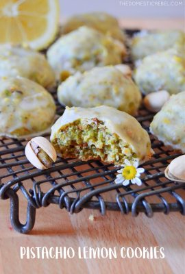 pistachio lemon snowball cookies on wire rack with pistachio nuts and daisies