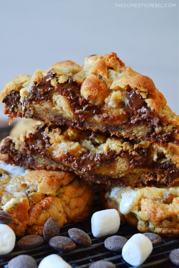 a cut open gooey s'mores cookie stacked with marshmallows and chocolate chips
