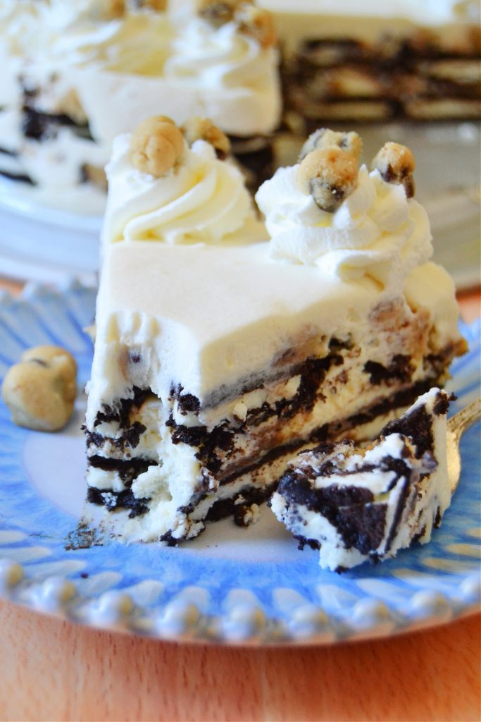 closeup slice of cookie dough oreo icebox cake with bite missing on blue plate