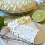 a piece of no bake margarita pie on a white plate with a fork and a lime wedge
