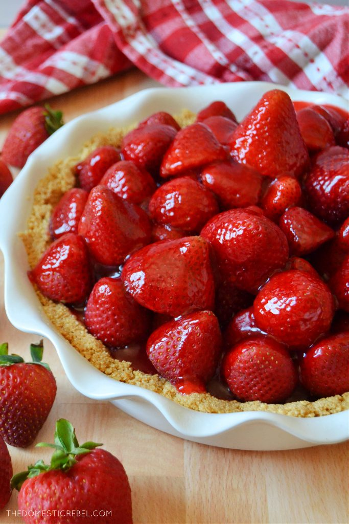 a strawberry pie in a white ruffled dish with a red towel in the background