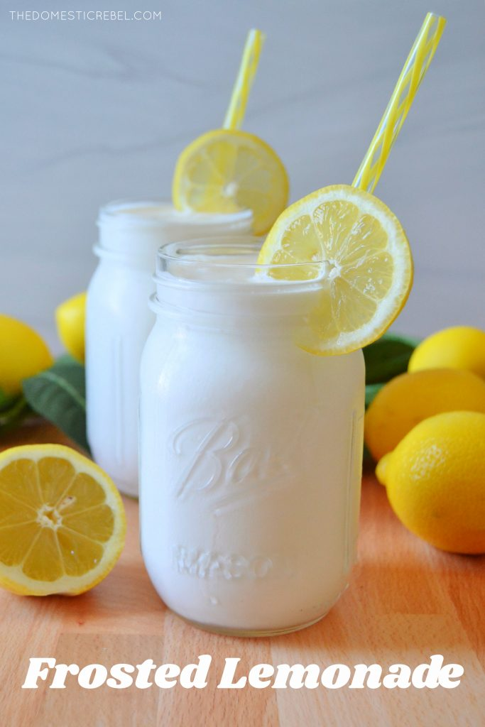 A mason jar with frosted lemonade, a lemon wheel and a yellow straw surrounded by lemons