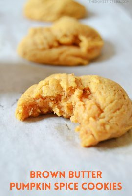 a brown butter pumpkin spice cookie with a bite missing on parchment paper
