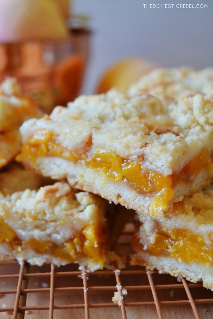 a closeup stack of peach crumble bars on a wire rack