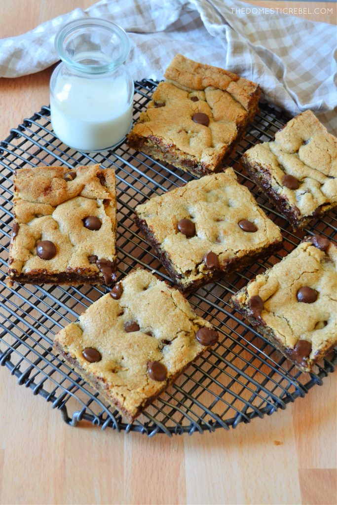 chocolate chip cookie bars arranged on a wire rack with a glass of milk