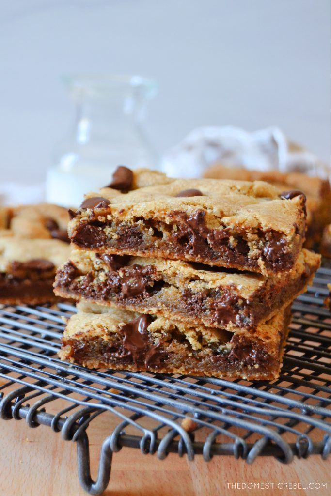 a gooey stack of three cookie bars on a wire rack