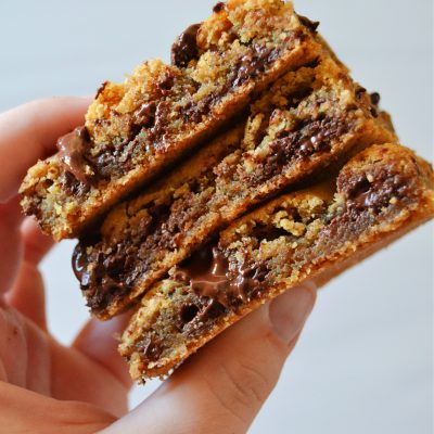 author holding a stack of three gooey chocolate chip cookie bars