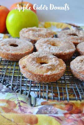 apple cider donuts on a cooling rack with apples in the background