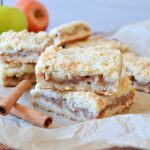 two apple crumble bars stacked on parchment paper with cinnamon sticks