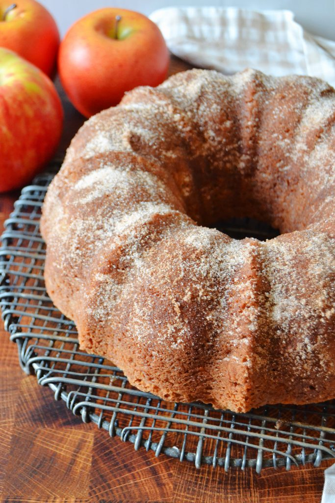 a whole apple cider doughnut cake on a wire rack with apples in the background