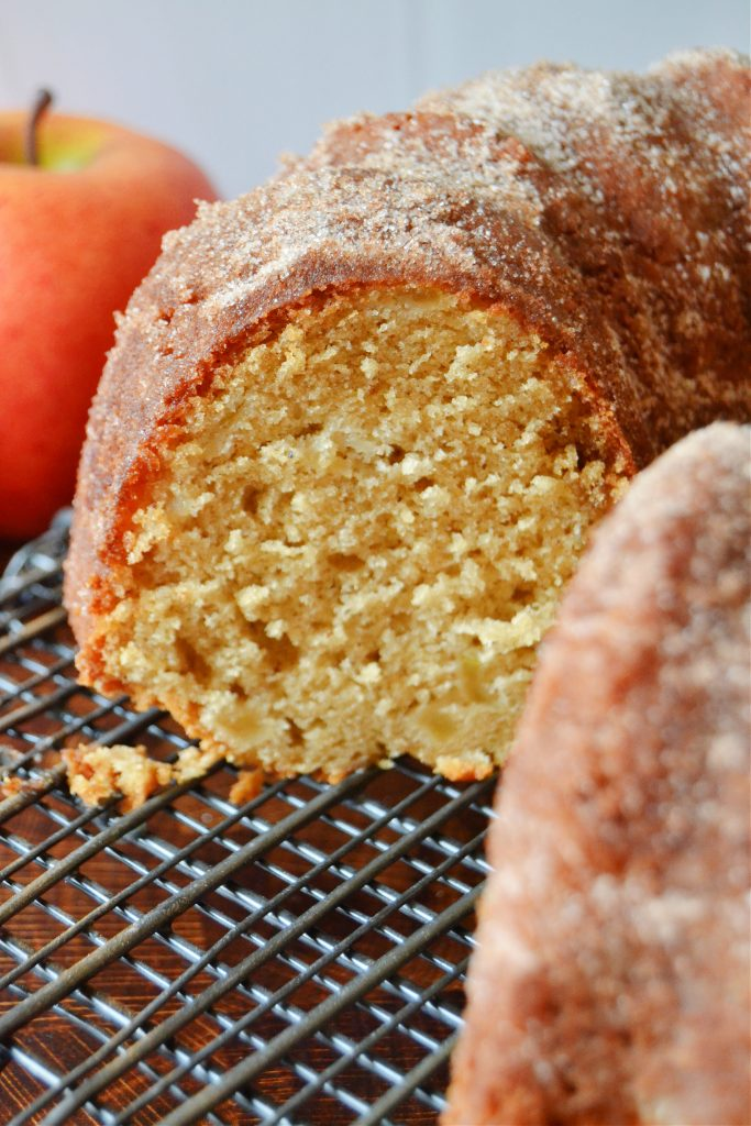 a side profile of a slice of apple cider doughnut cake on a wire rack