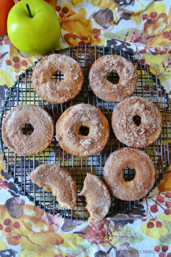 apple cider donuts arranged on a round wire rack with a green apple