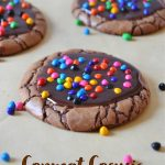 cosmic brownie cookies arranged on parchment paper with sprinkles in the background