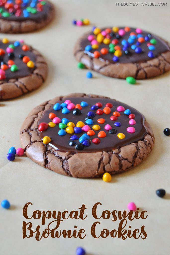 a cosmic brownie cookie arranged with other cookies on brown parchment with sprinkles