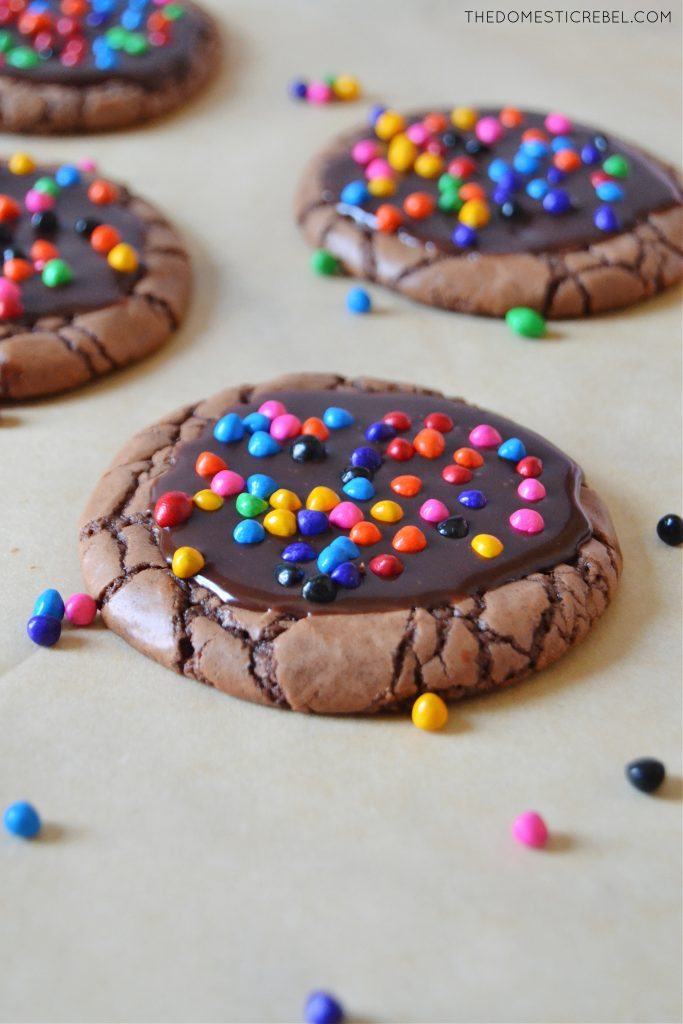 a cosmic brownie cookie on parchment paper surrounded by other cookies and sprinkles